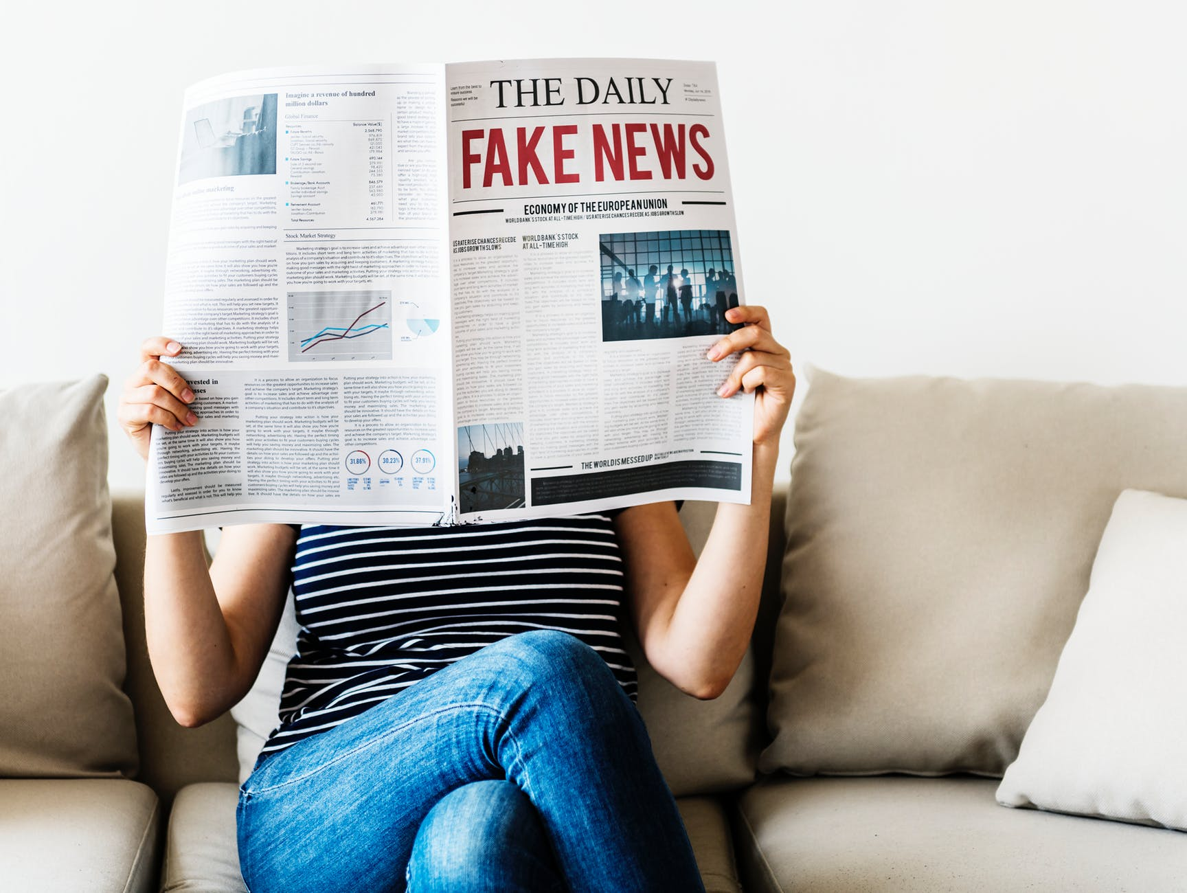 person reading the daily fake news newspaper sitting on gray couch